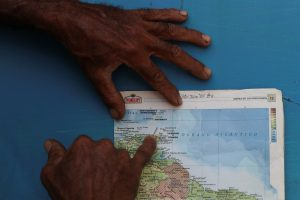 "A local resident points on a map at an area nicknamed the Dragon's Mouths, where Maroly Bastardo, an eight months pregnant woman, along with her children, her husband's sister, uncle and father, disappeared in the Caribbean Sea after boarding a smuggler's boat during an attempt to cross from Venezuela to Trinidad and Tobago, in Guiria, Venezuela, May 23, 2019. REUTERS/Ivan Alvarado SEARCH ""BASTARDO VENEZUELA"" FOR THIS STORY. SEARCH ""WIDER IMAGE"" FOR ALL STORIES."
