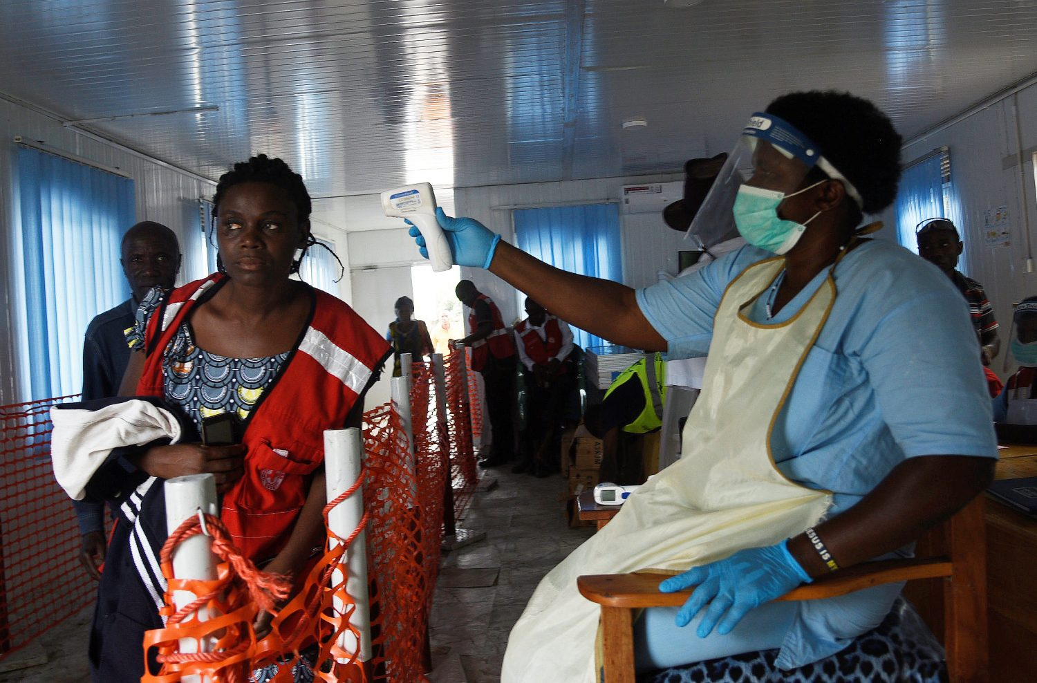 A health worker checks the temperature of a woman as she crosses the Mpondwe border point separating Uganda and the Democratic Republic of Congo as part of the ebola screening at the computerised Mpondwe Health Screening Facility in Mpondwe, Uganda June 13, 2019. REUTERS/Newton Nabwaya