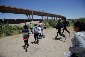 Migrants from Central America run towards the Rio Bravo river to cross and enter illegally into the United States to turn themselves in to request for asylum in El Paso, Texas, U.S., as seen from Ciudad Juarez, Mexico June 12, 2019. Picture taken June 12, 2019. REUTERS/Jose Luis Gonzalez