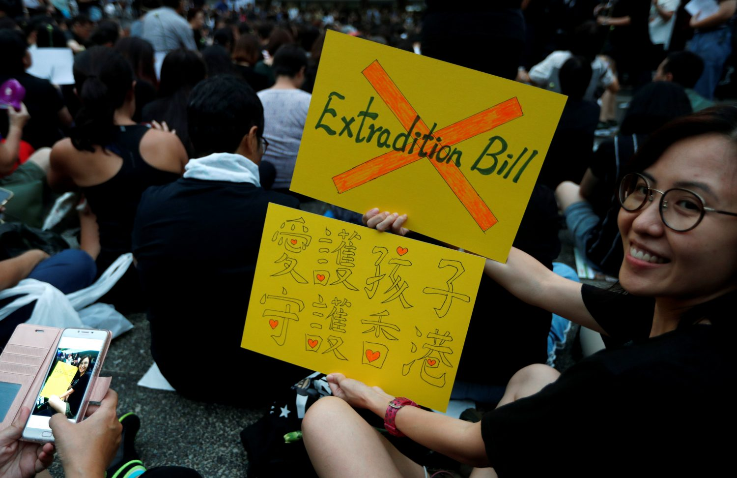 A woman holds placards as she attends a rally in support of demonstrators protesting against proposed extradition bill with China, in Hong Kong, China, June 14, 2019. REUTERS/Jorge Silva