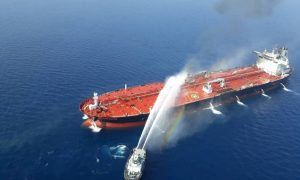 FILE PHOTO: An Iranian navy boat tackles a fire on an oil tanker after it was attacked in the Gulf of Oman, June 13, 2019. Tasnim News Agency/Handout via REUTERS