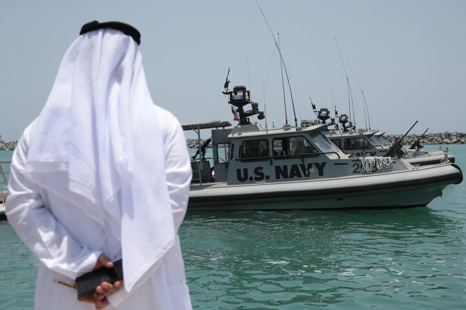 An Emirati official watches members of the U.S. Navy Fifth Fleet as they prepare to escort journalists to the Japanese-owned Kokuka Courageous tanker at a U.S. NAVCENT facility near the port of Fujairah, United Arab Emirates June 19, 2019. REUTERS/Christopher Pike