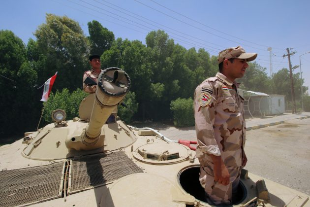 Iraqi soldiers sit on a tank at the entry of Zubair oilfield after a rocket struck the site of residential and operations headquarters of several oil companies at Burjesia area, in Basra, Iraq June 19, 2019. REUTERS/Essam Al-Sudani