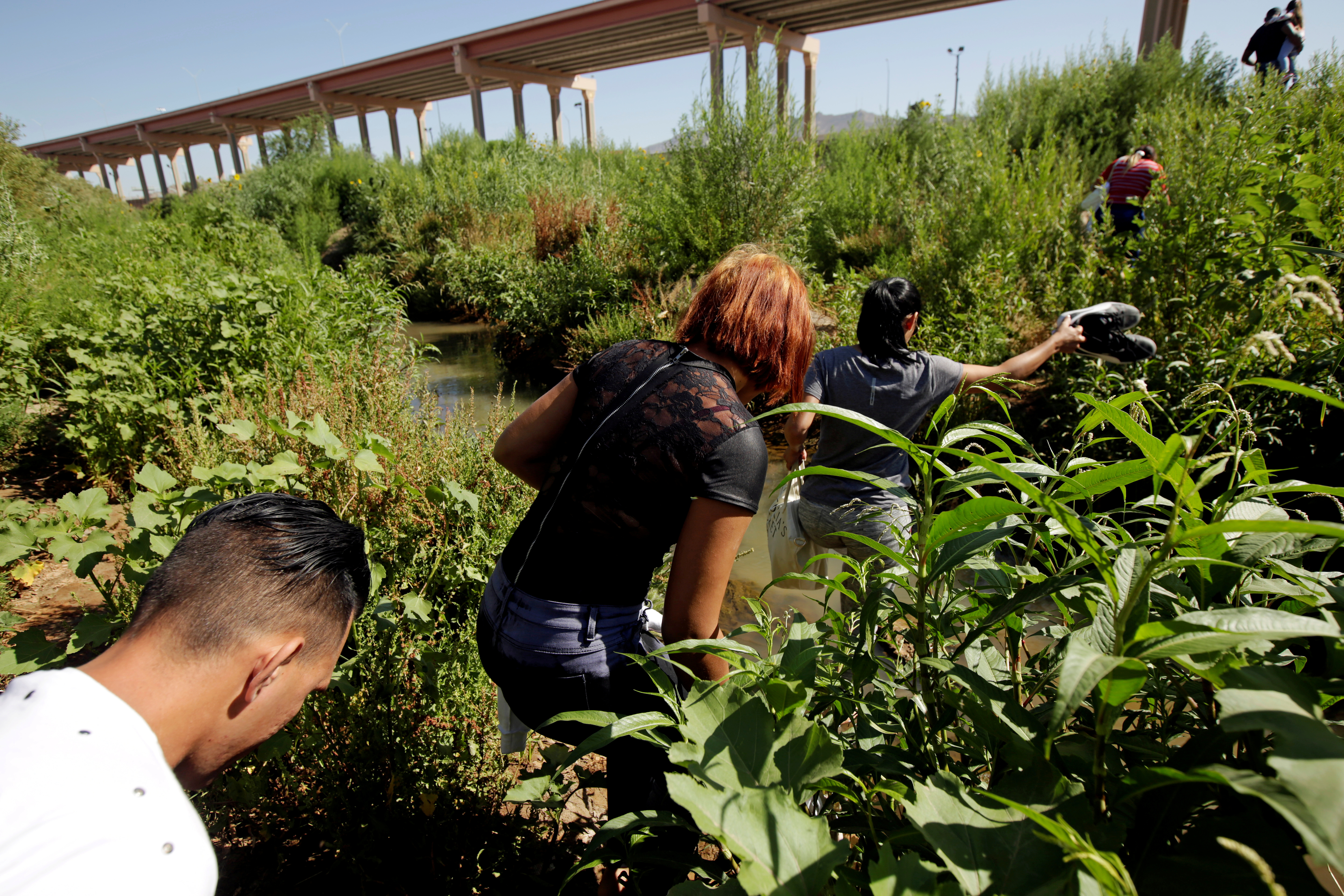 FILE PHOTO: Migrants from Cuba are seen on the banks of the Rio Bravo river as they cross illegally into the United States to turn themselves in to request asylum in El Paso, Texas, as seen from Ciudad Juarez, Mexico June 6, 2019. REUTERS/Jose Luis Gonzalez/File Photo