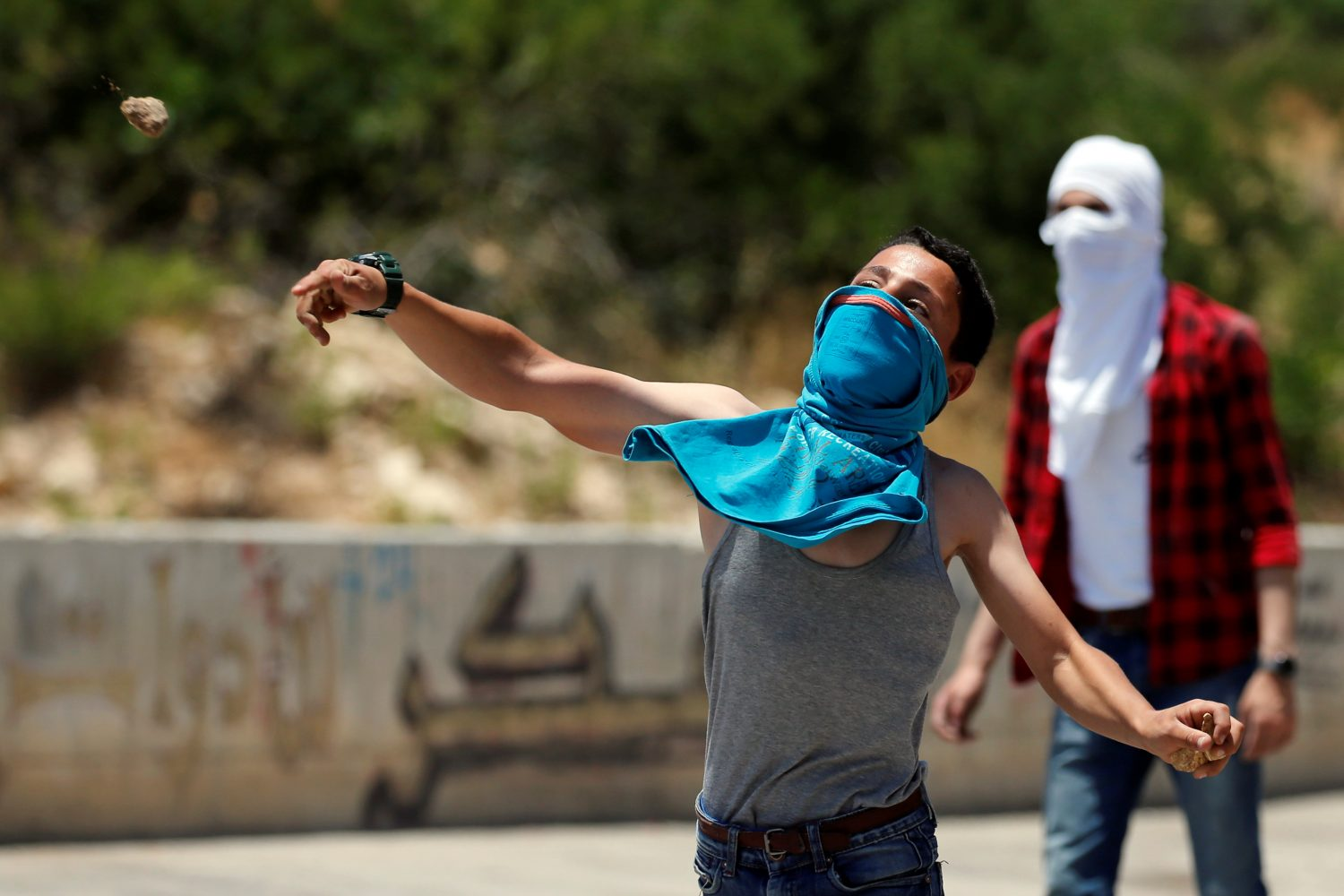 A Palestinian boy hurls stones at Israeli forces during clashes at a protest against Bahrain's workshop for U.S. peace plan, near Hebron, in the Israeli-occupied West Bank June 24, 2019. REUTERS/Mussa Qawasma