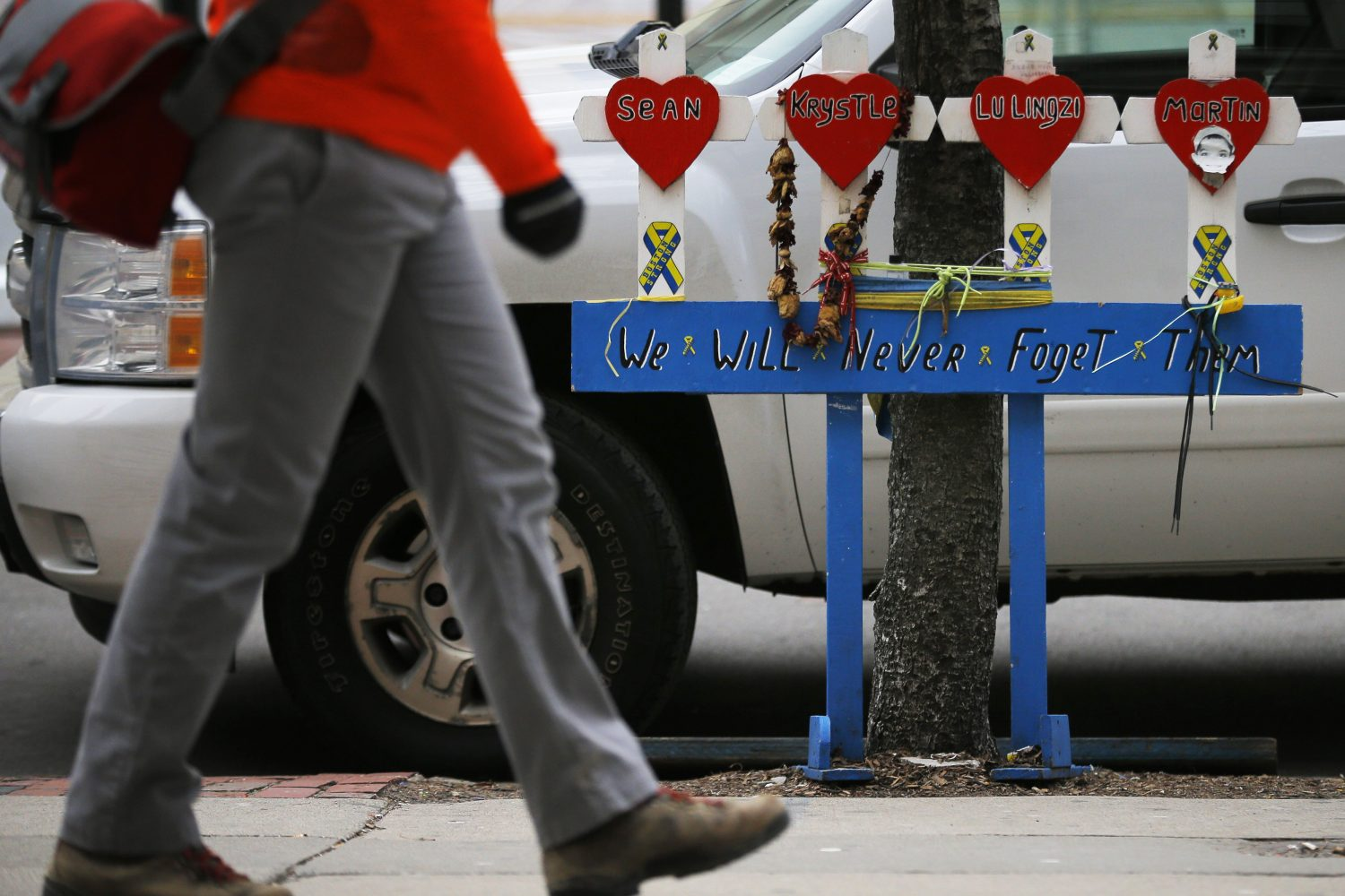 FILE PHOTO: A pedestrian walks past a memorial for the victims of the Boston Marathon bombings and its aftermath near the race's finish line, on the second day of jury selection in the trial of accused Boston Marathon bomber Dzhokhar Tsarnaev in Boston, Massachusetts January 6, 2015. REUTERS/Brian Snyder