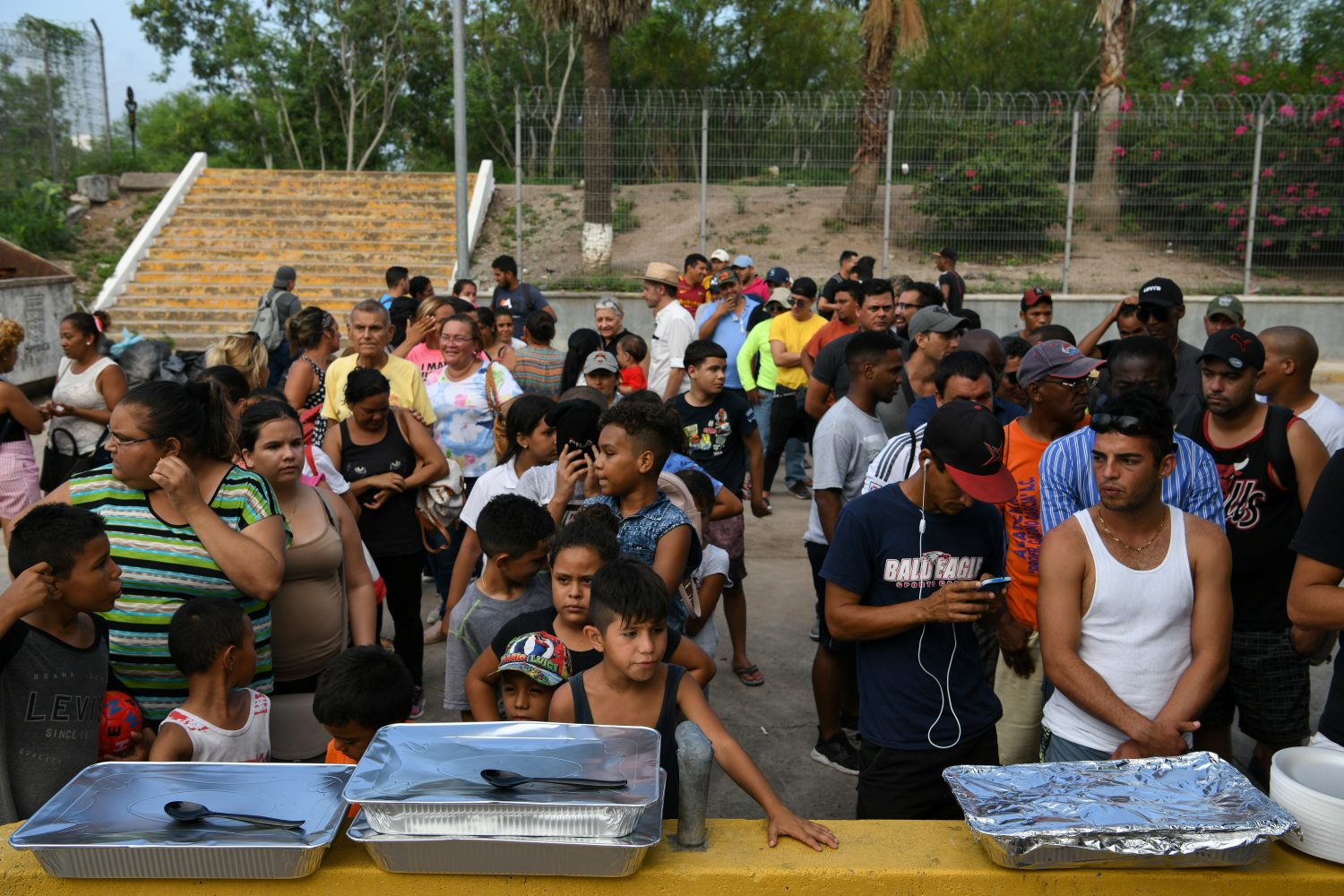 Asylum seekers waiting in hopes of being let through the nearby U.S. port of entry line up for a meal provided by volunteers at a makeshift migrant camp by the Gateway International Bridge in Matamoros, Tamaulipas, Mexico, June 26, 2019. REUTERS/Loren Elliott