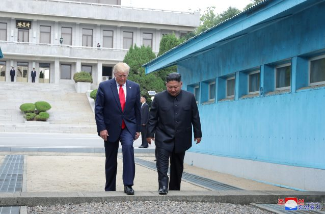 U.S. President Donald Trump and North Korean leader Kim Jong Un cross over a military demarcation line at the demilitarized zone (DMZ) separating the two Koreas, in Panmunjom, South Korea, June 30, 2019. KCNA via REUTERS