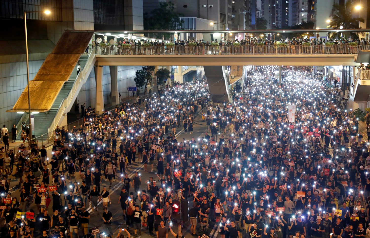 Anti-extradition bill protesters use the flashlights from their phones as they march during the anniversary of Hong Kong's handover to China in Hong Kong, China July 1, 2019. REUTERS/Tyrone Siu