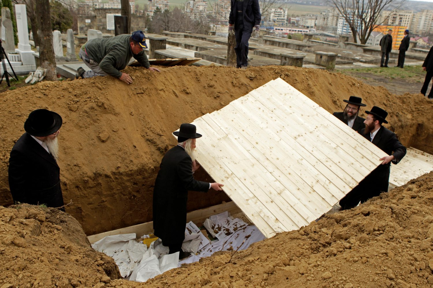 FILE PHOTO: Rabbis from England and the United States prepare a grave to bury the remains of dozens of Jews in a cemetery in Iasi, Romania, April 4, 2011. REUTERS/Bogdan Cristel/File Photo