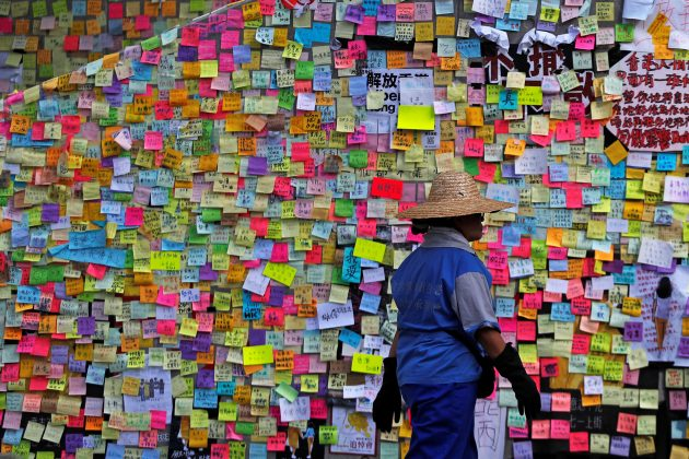 A worker walks past post-it notes scribbled with messages, left behind by protesters on the walls of the Legislative Council, a day after protesters broke into the building, in Hong Kong, China July 2, 2019. REUTERS/Jorge Silva