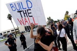 FILE PHOTO: Trump supporters hug after U.S. President Donald Trump's motorcade drove past them following his viewing of border wall prototypes in San Diego, California, U.S., March 13, 2018. REUTERS/Mike Blake/File Photo