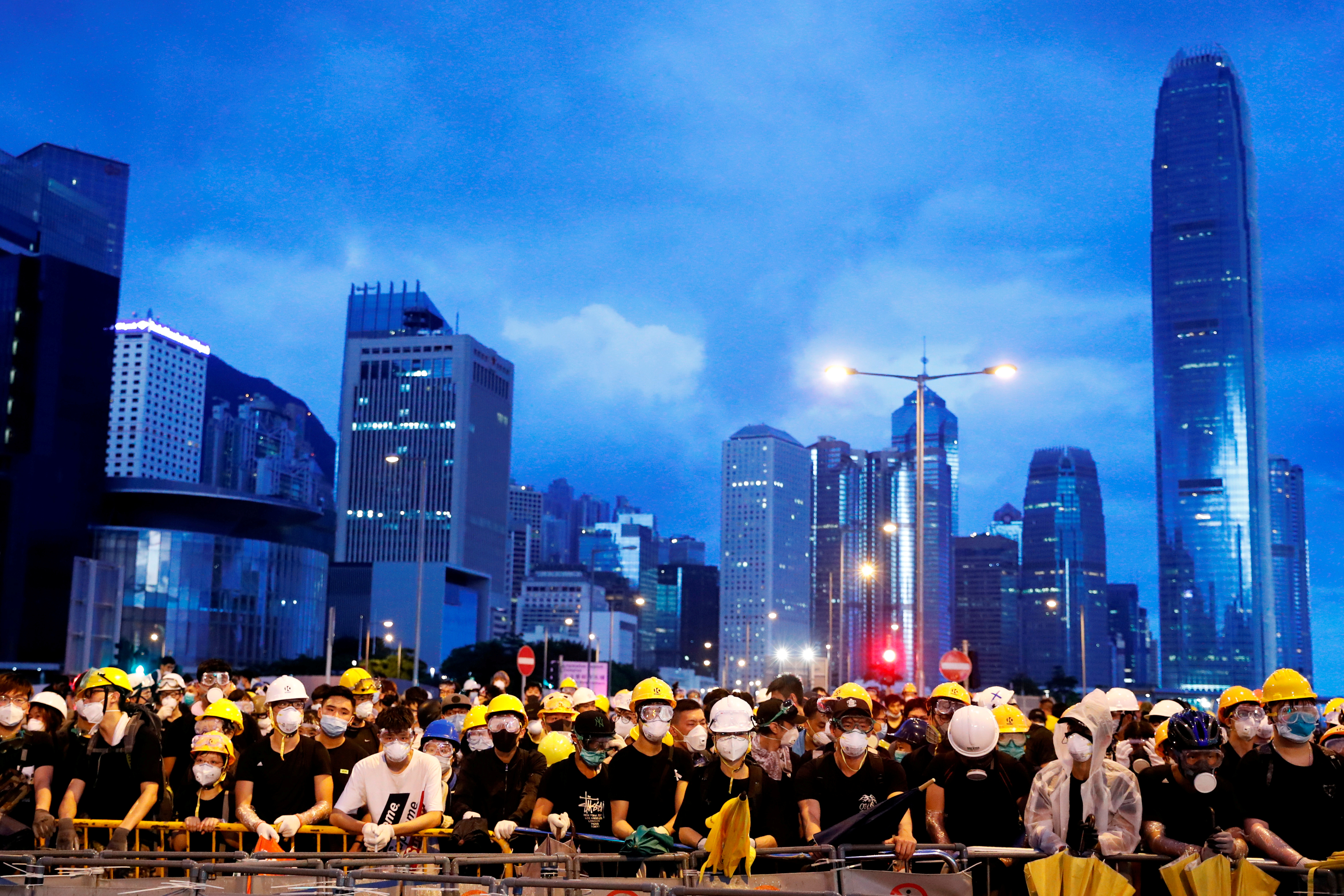 FILE PHOTO: Anti-extradition bill protesters stand behind a barricade during a demonstration near a flag raising ceremony for the anniversary of Hong Kong handover to China in Hong Kong, China July 1, 2019. REUTERS/Tyrone Siu/File Photo