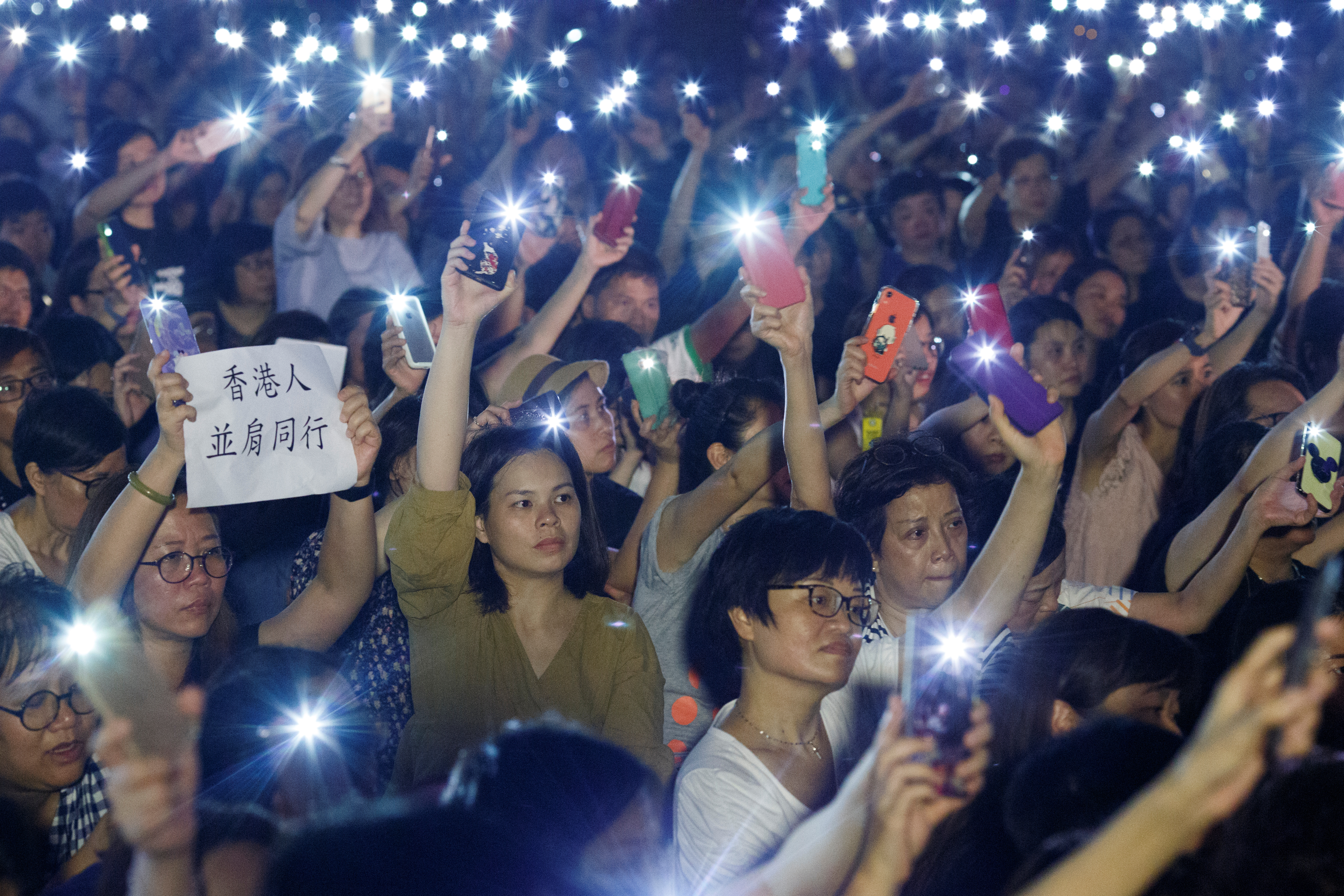 People wave flashlights during a gathering of Hong Kong mothers to show their support for the city's young pro-democracy protesters in Hong Kong, China July 5, 2019. REUTERS/Thomas Pet
