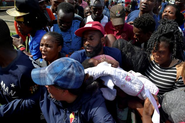 FILE PHOTO: A migrant from Cameroon holds his baby while trying to enter the Siglo XXI immigrant detention center to request humanitarian visas, issued by the Mexican government, to cross the country towards the United States, in Tapachula, Mexico June 27, 2019. REUTERS/Jose Torres/File Photo