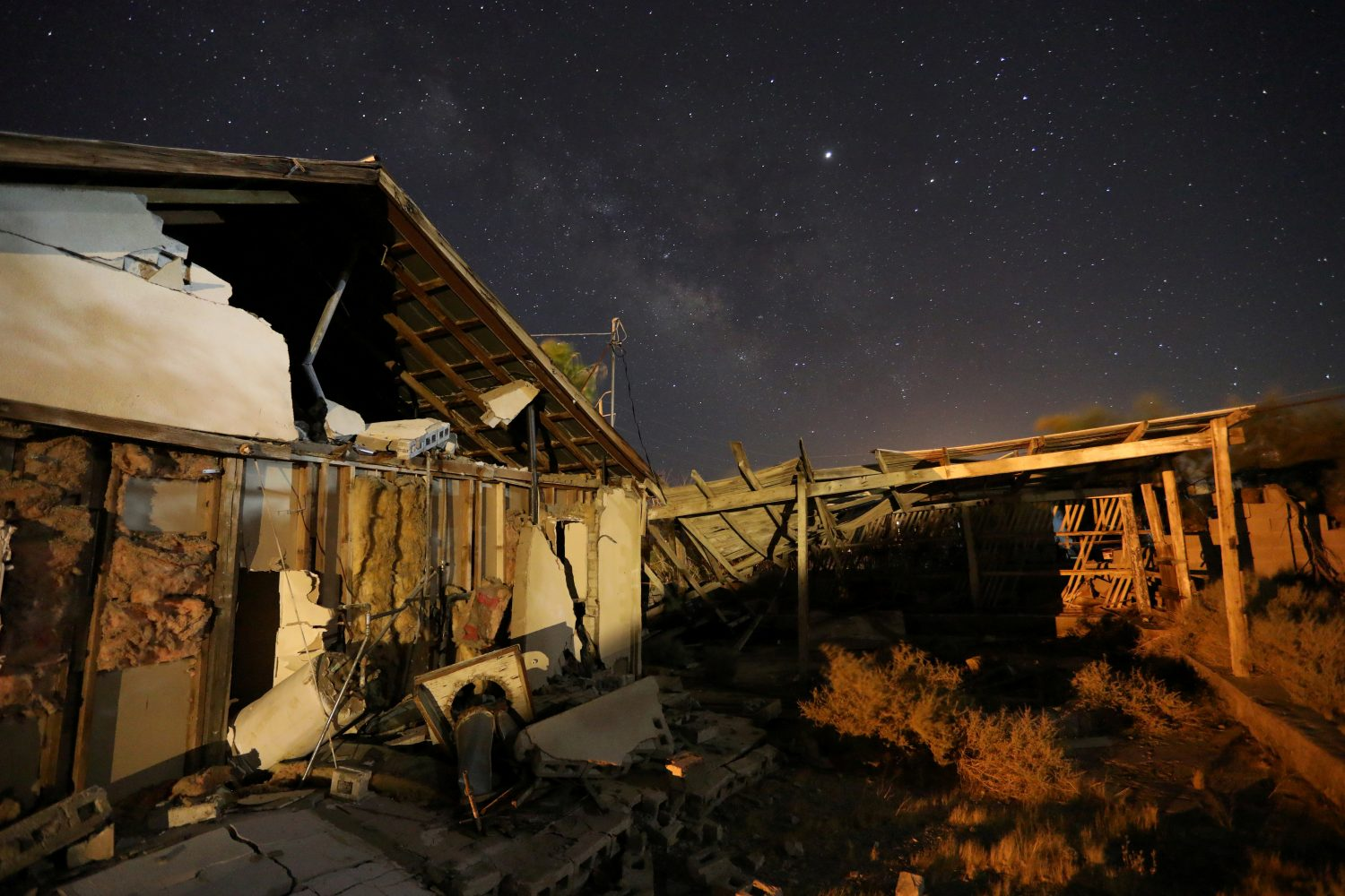 A house left destroyed by a powerful magnitude 7.1 earthquake, triggered by a 6.4 the previous day, is seen at night near the epicenter in Trona, California, U.S., July 6, 2019. REUTERS/David McNew