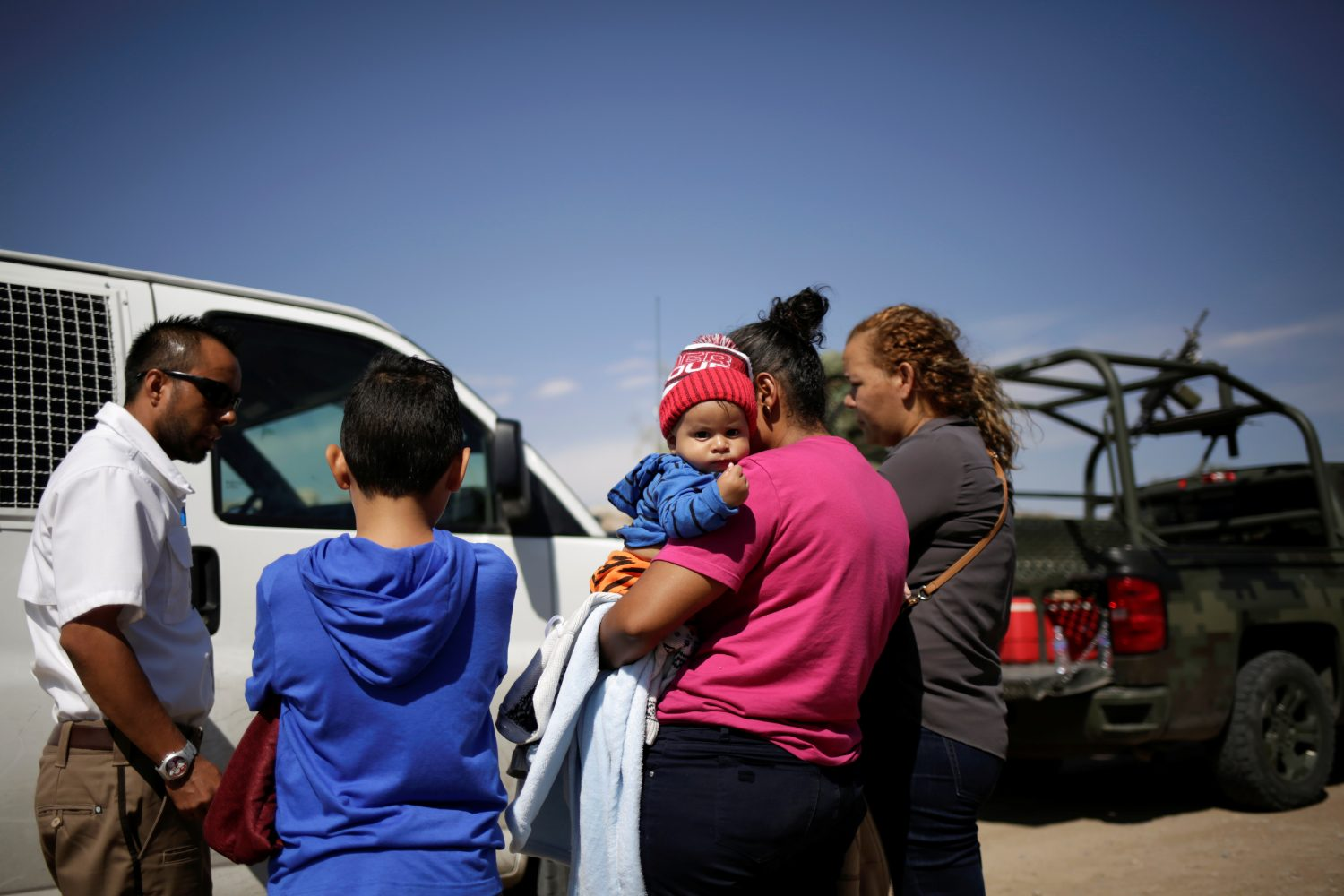 An agent of the National Migration Institute (INM) talks to Honduran migrants after being stopped from crossing the border into the United States by members of the Mexican National Guard, in Ciudad Juarez, Mexico June 28, 2019. REUTERS/Jose Luis Gonzalez