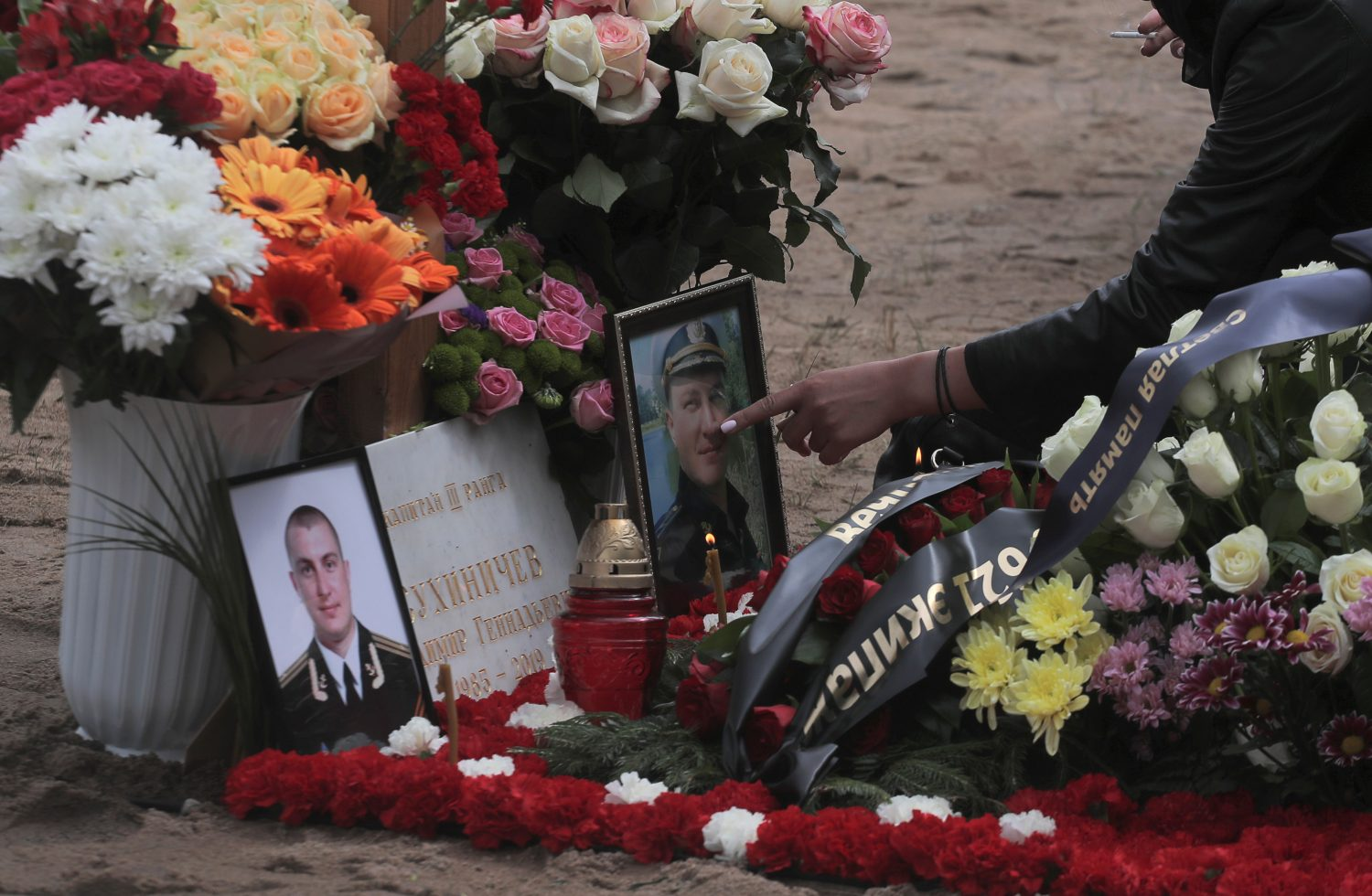 A mourner touches a photograph at the grave of Captain third rank Vladimir Sukhinichev during the funeral of Russian sailors, who were recently killed in a fire on a secret nuclear research submarine in the area of the Barents Sea, at Serafimovskoye cemetery in Saint Petersburg, Russia July 6, 2019. REUTERS/Anton Vaganov