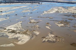 FILE PHOTO: Flooded farm fields are seen from an aerial photo taken while Nebraska Army National Guard Soldiers used a CH-47 Chinook helicopter to deliver multiple bales of hay to cattle isolated by historic flooding in Richland, Nebraska, U.S., March 20, 2019. Picture taken on March 20, 2019. Courtesy Lisa Crawford/Nebraska National Guard/Handout via REUTERS