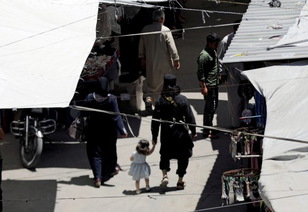 FILE PHOTO: A man with a gun holds the hand of a child as they walk in a souk in the city of Idlib, Syria May 25, 2019. REUTERS/Khalil Ashawi