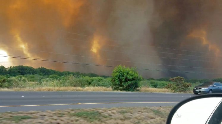 A thick plume of smoke hovers over a wildfire next to a road in Maui, Hawaii, in this still image taken from a July 11, 2019 video from social media. Drumnicodotcom/via REUTERS
