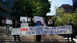 FILE PHOTO: People hold signs protesting China's treatment of the Uighur people, in Vancouver, British Columbia, Canada, May 8, 2019. REUTERS/Lindsey Wasson