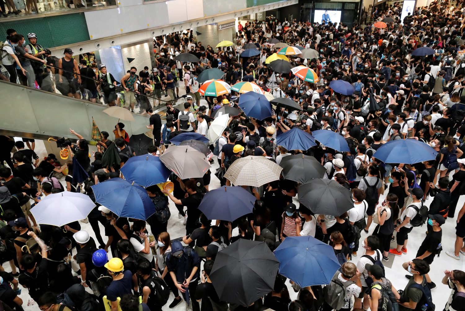 FILE PHOTO: Pro-democracy protesters hold umbrellas inside a mall as they face the riot police after a march at Sha Tin District of East New Territories, in Hong Kong, China July 14, 2019. REUTERS/Tyrone Siu/File Photo
