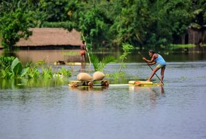 A man uses a makeshift raft to move his paddy to a safer place in a flooded area in Morigaon district in the northeastern state of Assam, India, July 16, 2019. REUTERS/Anuwar Hazarika
