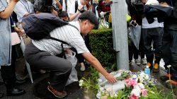 A man placed flowers near the torced Kyoto Animation building to mourn the victims of the arson attack, in Kyoto, Japan, July 19, 2019. REUTERS/Kim Kyung-Hoon
