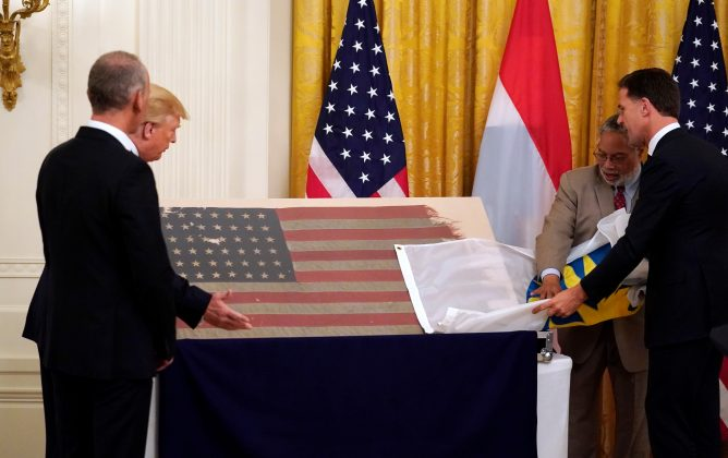 U.S. President Donald Trump, Dutch art collector Bert Kreuk, Netherlands' Prime Minister Mark Rutte and Smithsonian Secretary Lonnie Bunch look at a flag that flew on the first U.S. invading ship on D-Day during a White House ceremony after it was donated by Kreuk to the Smithsonian National Museum of American History in Washington, U.S., July 18, 2019. REUTERS/Kevin Lamarque
