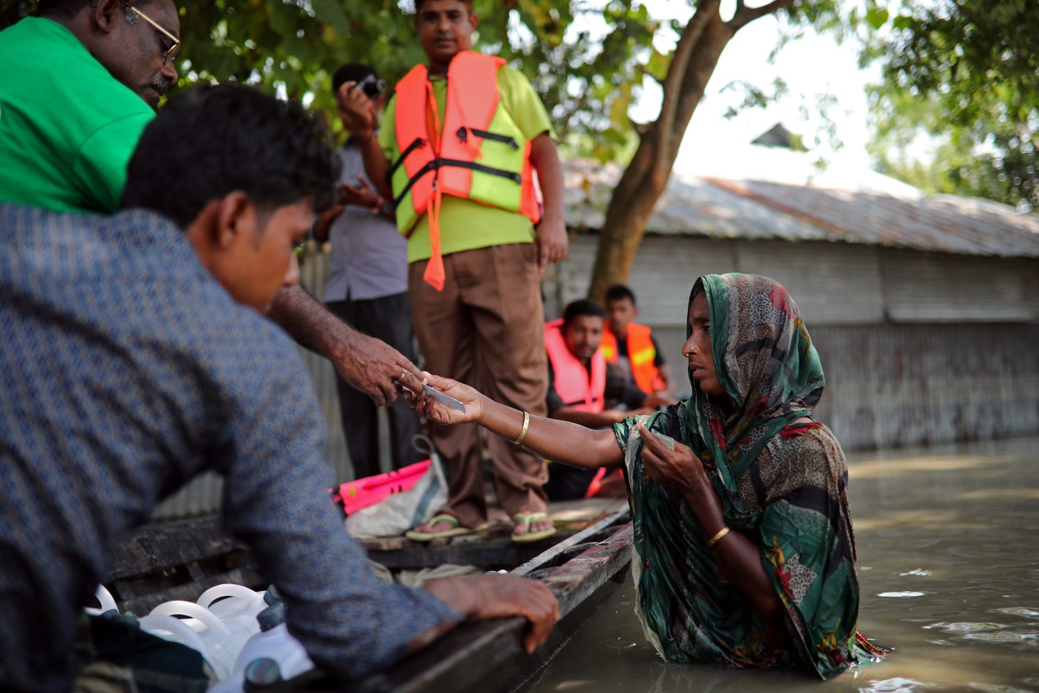 Flood-affected people receives water purifying tablets from volunteers in Jamalpur, Bangladesh, July 21, 2019. REUTERS/Mohammad Ponir Hossain