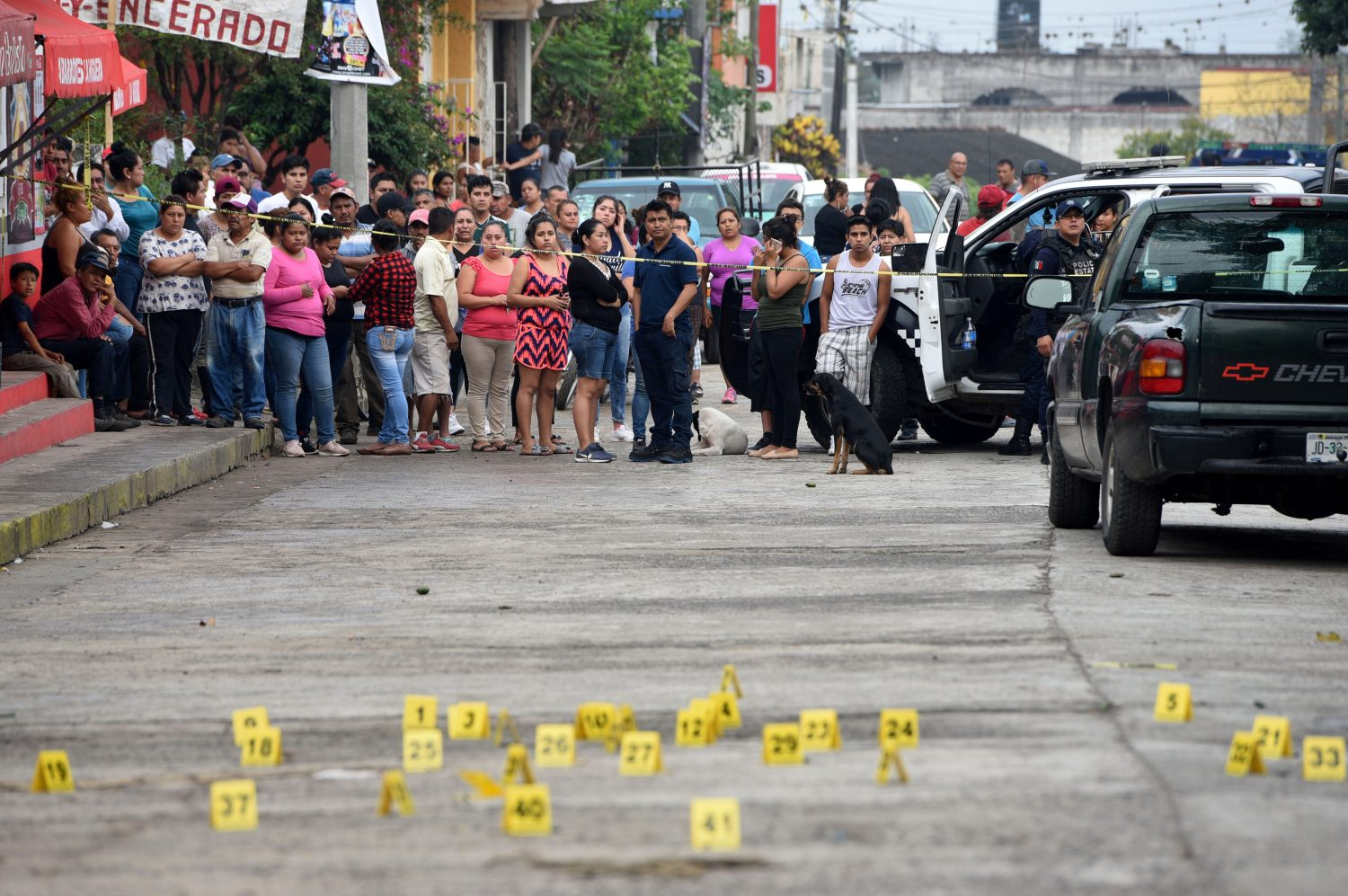 FILE PHOTO: People stand near bullet casings on the ground at a crime scene after a shootout in the municipality of Tuzamapan, in the Mexican state of Veracruz, Mexico, May 16, 2019. REUTERS/Yahir Ceballos/File Photo
