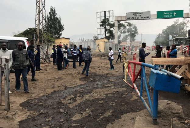 Congolese customs agents gather at the gate barriers at the border crossing point with Rwanda following its closure over ebola threat in Goma, eastern Democratic Republic of Congo, August 1, 2019. REUTERS/Djaffer Sabiti