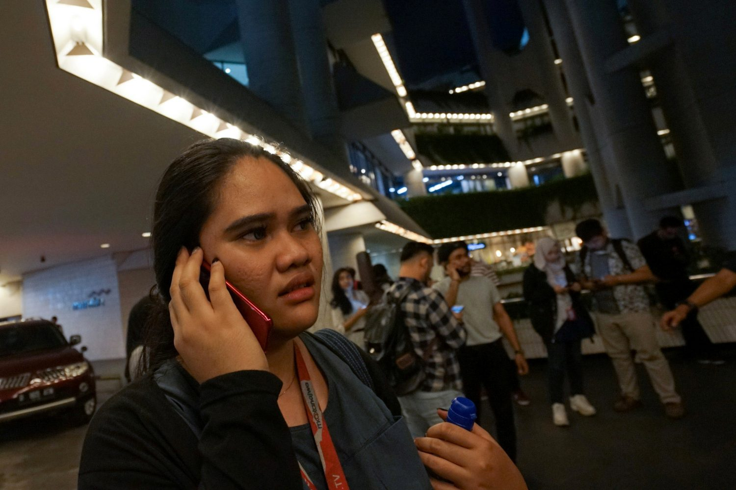 A woman uses a phone as she leaves an office building, following an earthquake hit in Jakarta, Indonesia, August 2, 2019 in this photo taken by Antara Foto. Antara Foto/Dwi Prasetya/ via REUTERS