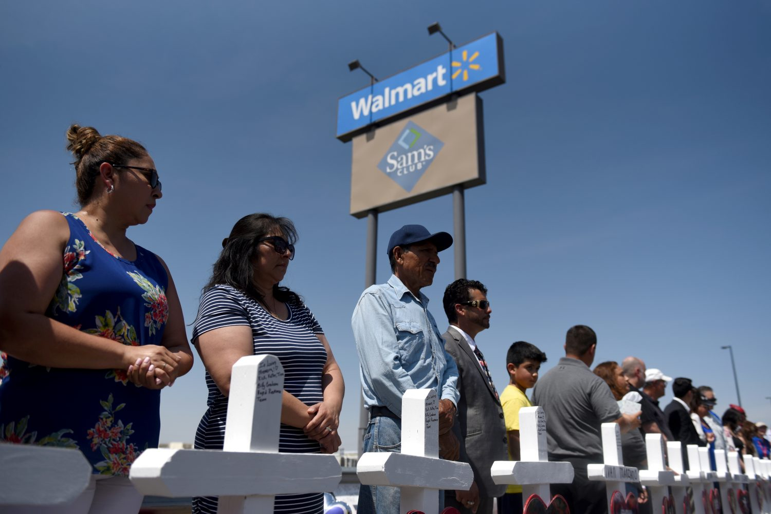 FILE PHOTO: People pray next to a row of crosses representing each of the victims at a growing memorial site two days after a mass shooting at a Walmart store in El Paso, Texas, U.S. August 5, 2019. REUTERS/Callaghan O'Hare/File Photo