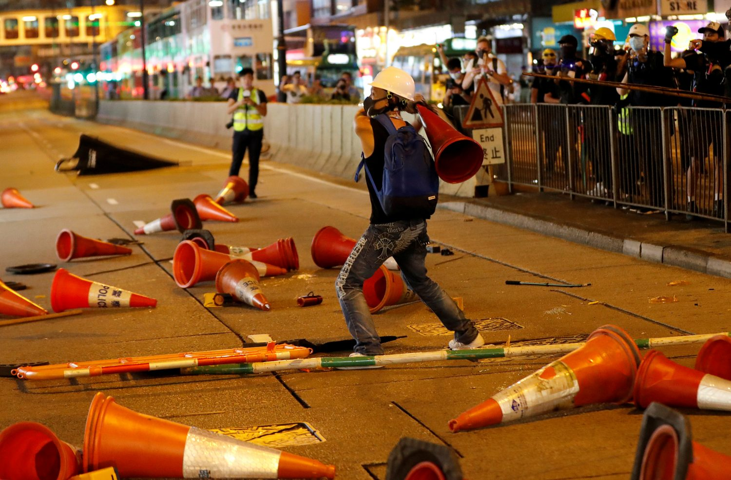A demonstrator throws a traffic cone at a group of people opposing the anti-government protesters, during a demonstration in support of the city-wide strike and to call for democratic reforms in Hong Kong, China, August 5, 2019. REUTERS/Kim Kyung-Hoon