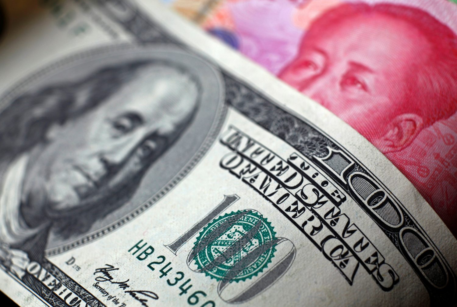 FILE PHOTO: U.S. Dollar and China Yuan notes are seen in this picture illustration June 2, 2017. REUTERS/Thomas White/Illustration/File Photo/File Photo