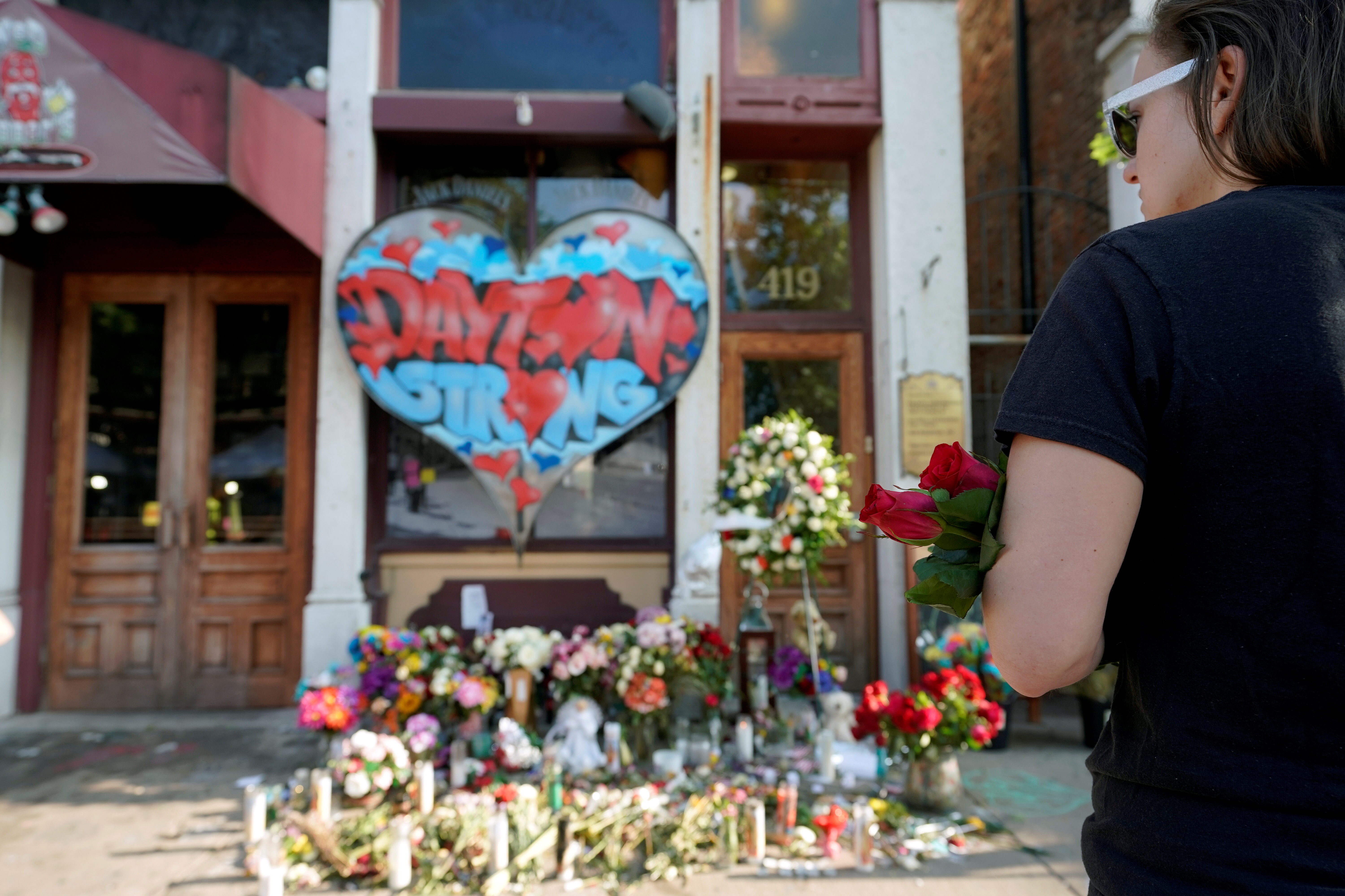 A Oregon District resident stands at a memorial for those killed during Sunday morning's a mass shooting in Dayton, Ohio, U.S. August 7, 2019. REUTERS/Bryan Woolston