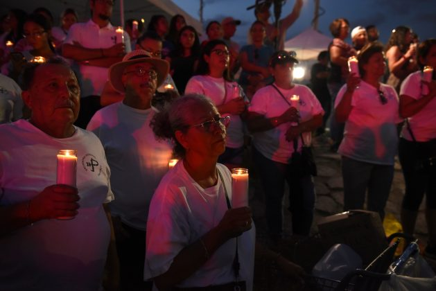 A group of people hold candles during a vigil at a memorial four days after a mass shooting at a Walmart store in El Paso, Texas, U.S. August 7, 2019. REUTERS/Callaghan O'Hare