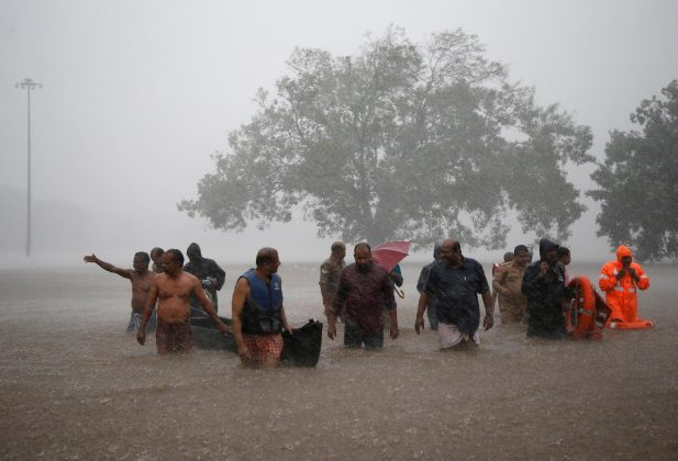 Members of a rescue team wade through a water-logged area during heavy rains on the outskirts of Kochi in the southern state of Kerala, India, August 8, 2019. REUTERS/Sivaram V