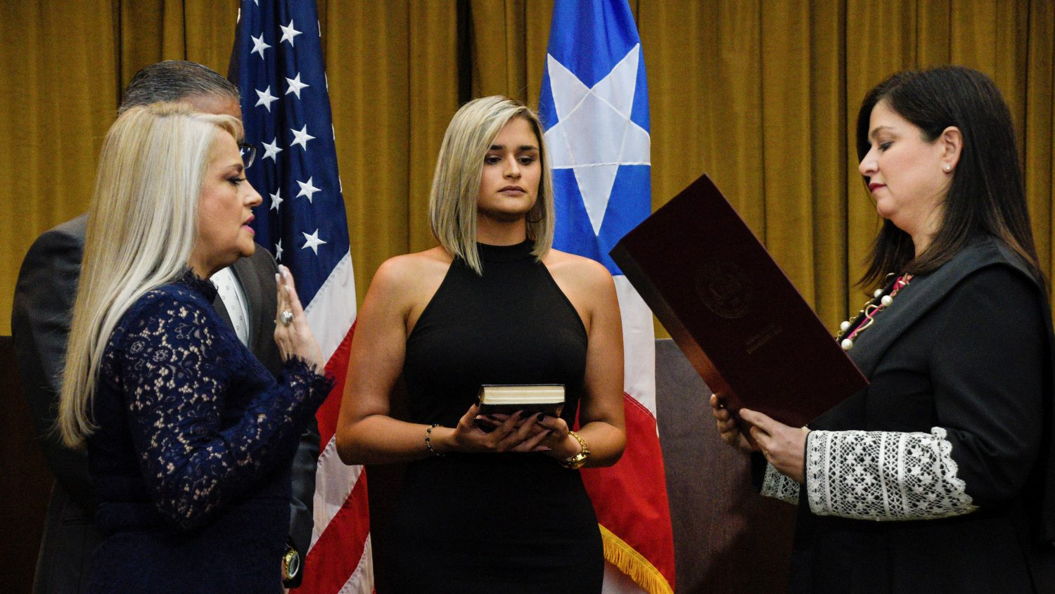 FILE PHOTO: Wanda Vazquez, former Secretary of Justice, is sworn in as Governor of Puerto Rico by Supreme Court Justice Maite Oronoz after Pedro Pierluisi's former oath was declared unconstitutional by the Supreme Court of Puerto Rico, in San Juan, Puerto Rico, August 7, 2019. Also pictured are Vazquez's husband Jorge Diaz (back L) and their daughter, Beatriz Diaz. REUTERS/Gabriella N. Baez/File Photo