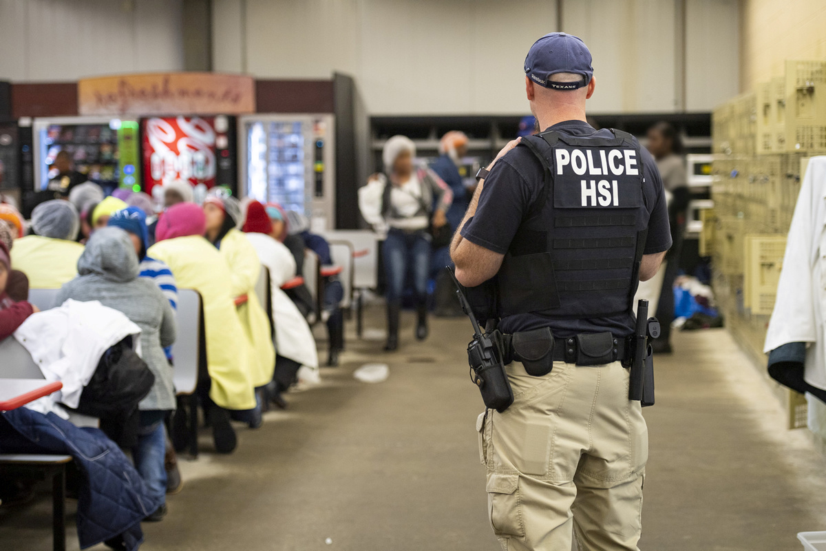 FILE PHOTO: Homeland Security Investigations (HSI) officers from Immigration and Customs Enforcement (ICE) look on after executing search warrants and making arrests at an agricultural processing facility in Canton, Mississippi, U.S. in this August 7, 2019 handout photo. Immigration and Customs Enforcement/Handout via REUTERS/File Photo