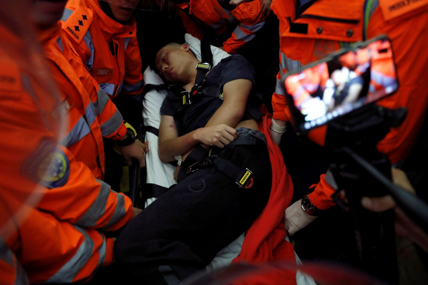 Medics attempt to remove an injured man who anti-government protesters said was a Chinese policeman during a mass demonstration at the Hong Kong international airport, in Hong Kong, China, August 13, 2019. REUTERS/Tyrone Siu