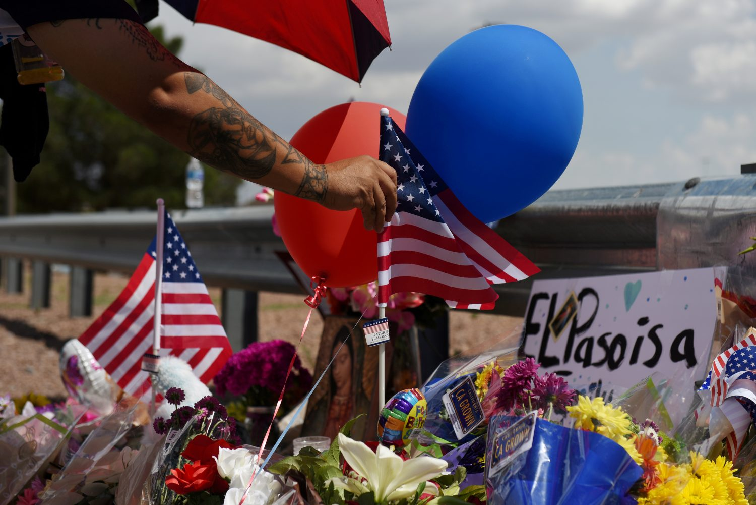 FILE PHOTO: A man places an American flag in the pile of flowers that has gathered a day after a mass shooting at a Walmart store in El Paso, Texas, U.S. August 4, 2019. REUTERS/Callaghan O'Hare/File Photo