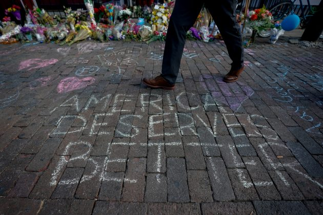 FILE PHOTO: A man walks past a memorial for those killed in a mass shooting in Dayton, Ohio, U.S. August 7, 2019. REUTERS/Bryan Woolston/File Photo