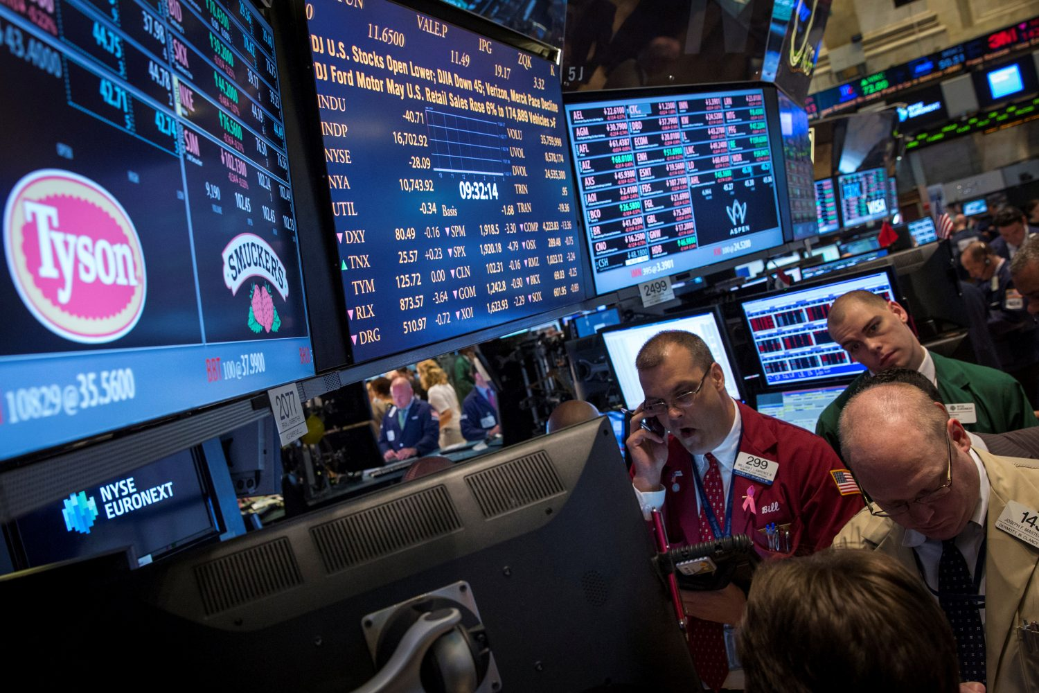FILE PHOTO: Traders gather at the post that trades Tyson Foods on the floor of the New York Stock Exchange June 3, 2014. REUTERS/Brendan McDermid/File Photo