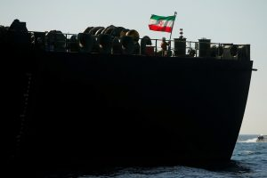 FILE PHOTO - A crew member raises the Iranian flag on Iranian oil tanker Adrian Darya 1, previously named Grace 1, as it sits anchored after the Supreme Court of the British territory lifted its detention order, in the Strait of Gibraltar, Spain, August 18, 2019. REUTERS/Jon Nazca