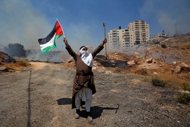 FILE PHOTO: A demonstrator holds a Palestinian flag and a cane during a protest against the Israeli demolitions of Palestinian homes in the village of Sur Baher which sits on either side of the Israeli barrier in East Jerusalem and the Israeli-occupied West Bank July 26, 2019. REUTERS/Mussa Qawasma