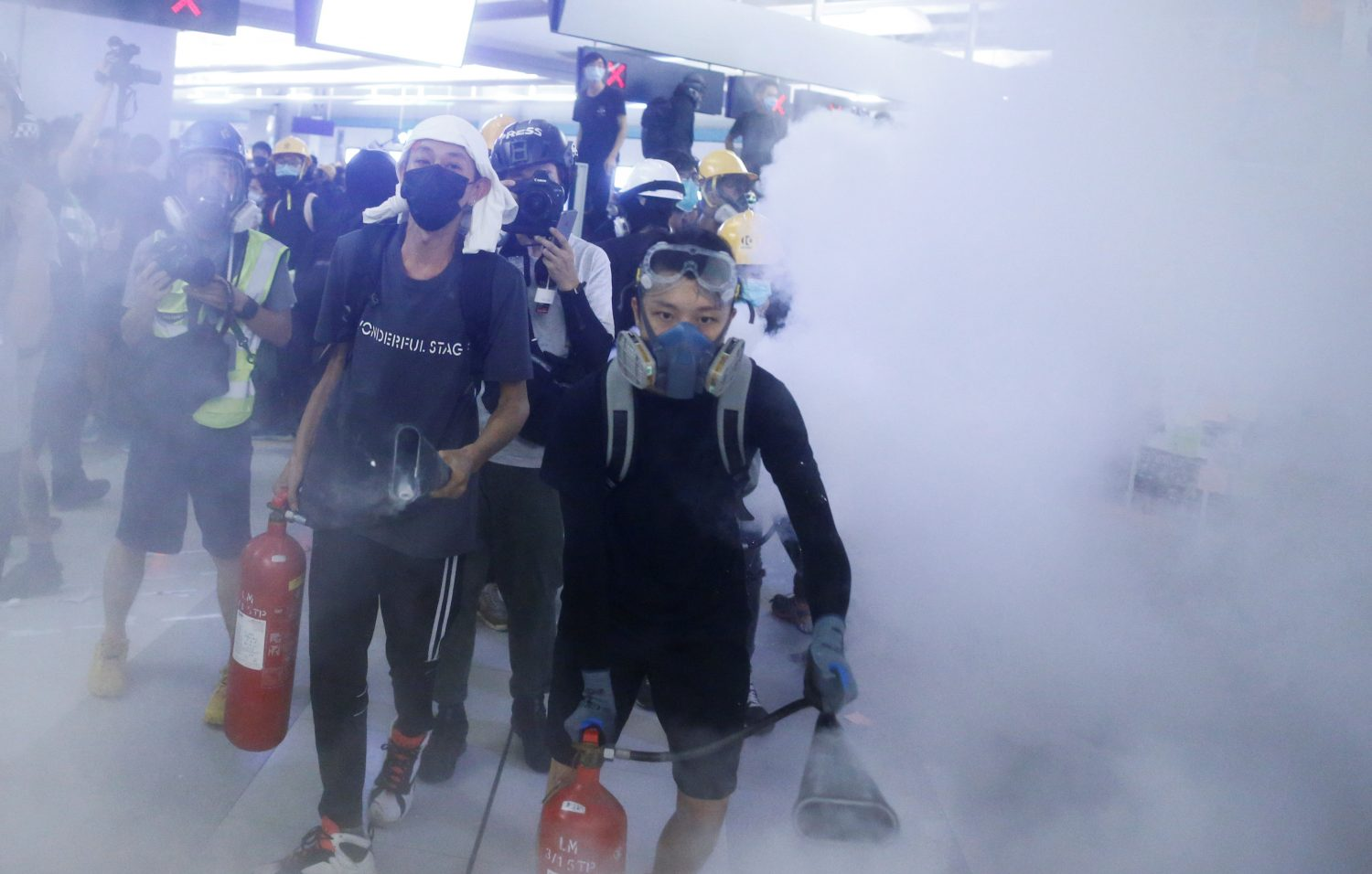 Protesters fire nitrogen extinguishers during a stand off at Yuen Long MTR station, the scene of an attack by suspected triad gang members a month ago, in Yuen Long, New Territories, Hong Kong, China August 21, 2019. REUTERS/Thomas Peter