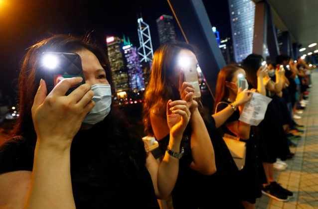 Protesters light up their smartphones as they form a human chain during a rally to call for political reforms in Hong Kong's Central district, China, August 23, 2019. REUTERS/Kai Pfaffenbach